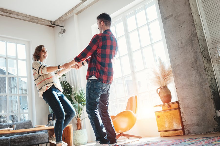 Personal Insurance - Happy Couple Having Fun and Dancing Together in the Living Room
